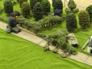 With all three Shermans burning, the Panther rolls over the top of the British infantry