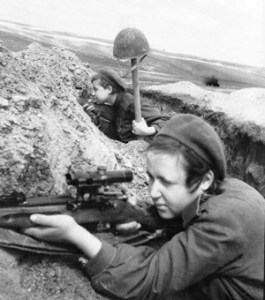 One female sniper watches through her scope while her spotter holds up a helmet on a stick