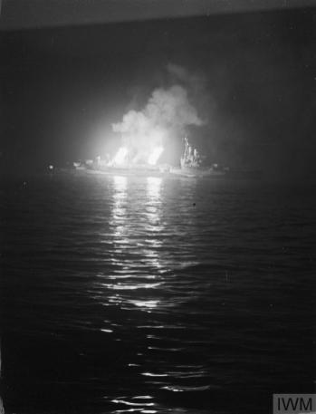 At night, a warship at sea is illuminated by the muzzle flash of its guns