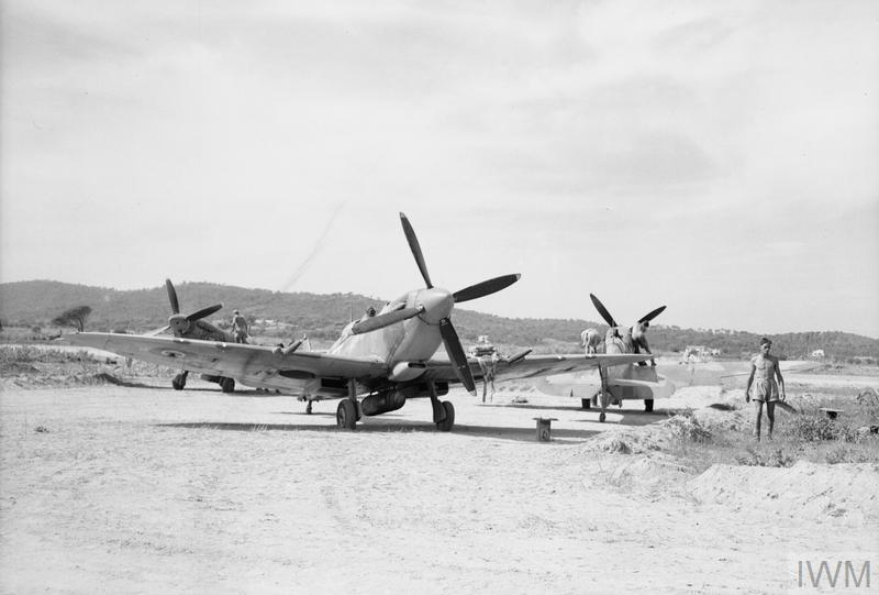 A Spitfire fighter taxis across an airfield