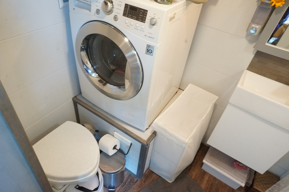 Tiny house bathroom with composting toilet and washer/dryer combo.