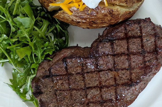 Steak with grill marks on a white place with a salad and baked potato