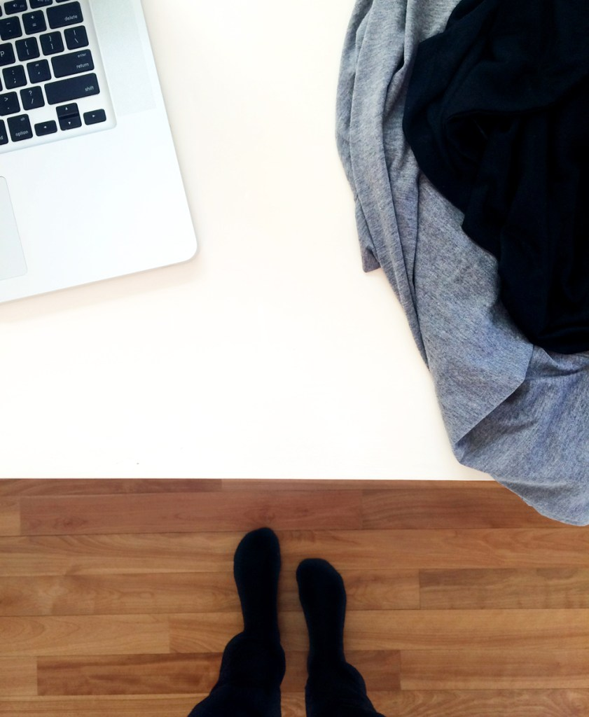 Looking down on a pile of clothes and laptop