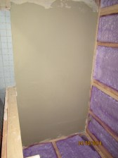 This is the bathroom, with a skim coat of thinset on it. The bathroom tile isn't as thick as the rest of the time, the skim coat builds up the height of the floor. This will be a small white hexagonal tile.