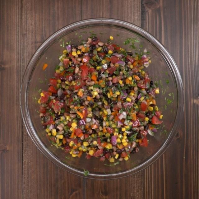 Mixing cowboy caviar in bowl