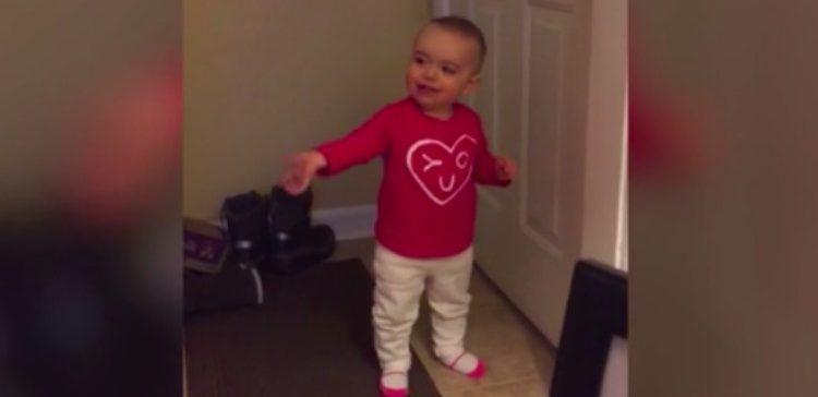 toddler wearing pink shirt standing by door