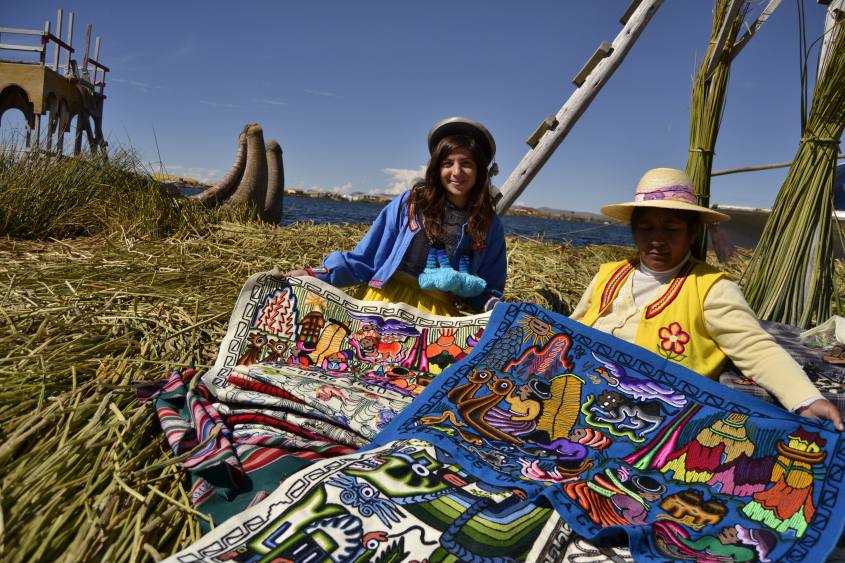 Artigiana Uros che mostra i suoi prodotti sull'Foto con vestiti tipici degli Uros sulle Islas Flotantes (Isole Galleggianti) in Perù