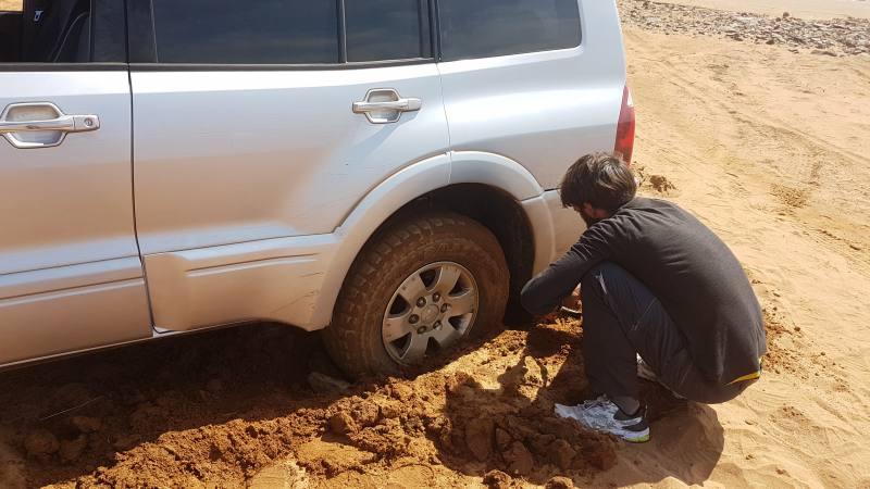 Leo che libera le ruote dell'auto dal fango dopo esserci insabbiati