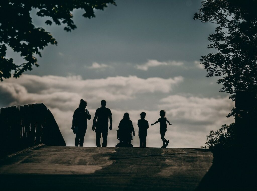 Silhouette of a family enjoying a day at the zoo, including one person with limited mobility.