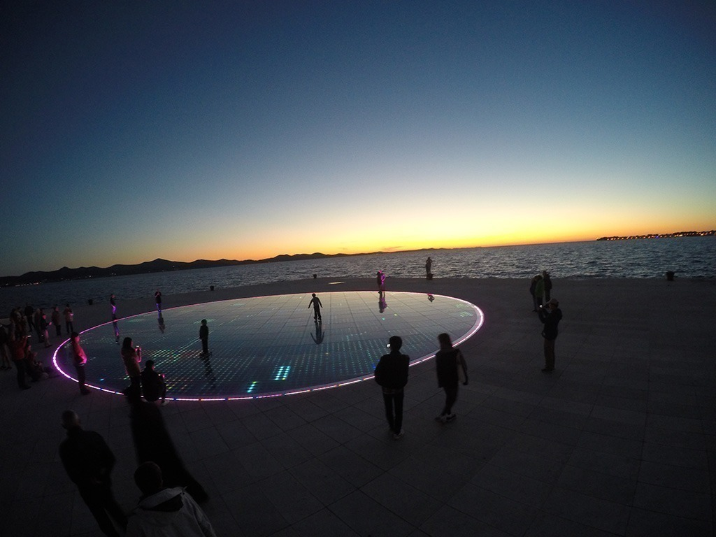 pôr do sol em Zadar, com vista para o mar e painel luminoso de led, Croácia