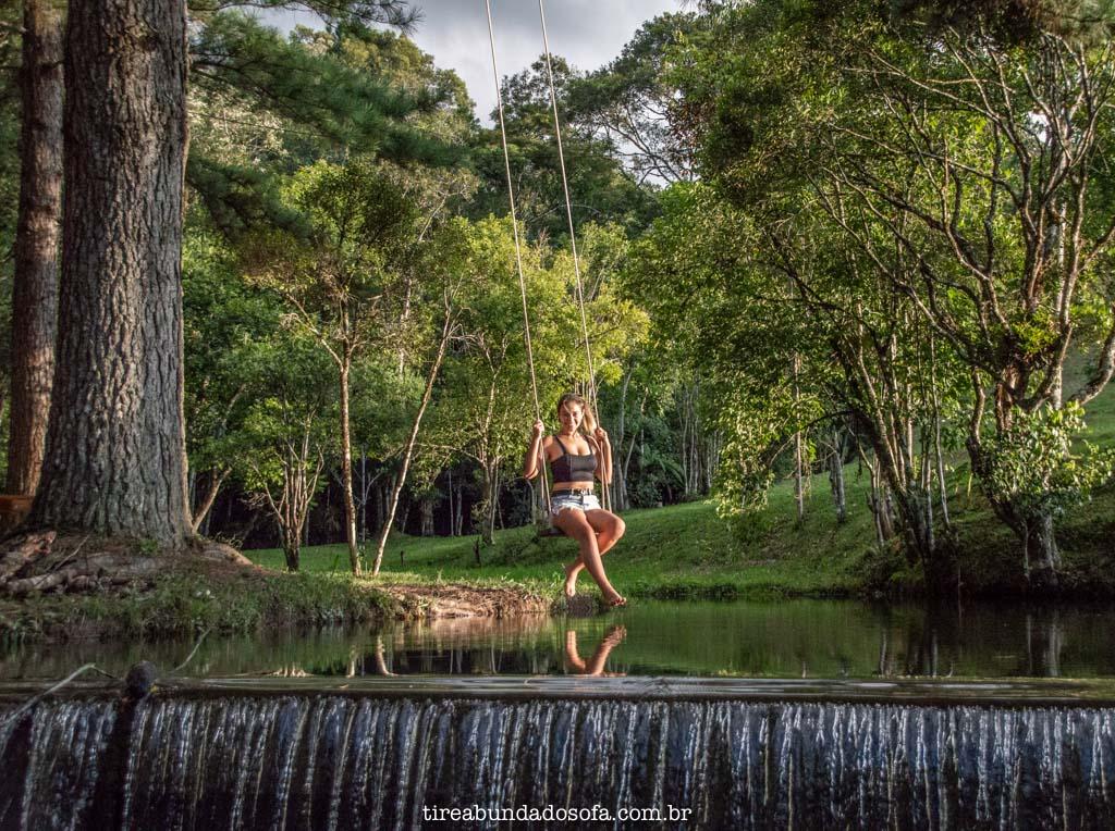 moça se balançando sobre a água, no camping e cachoeira paulista, em dr pedrinho