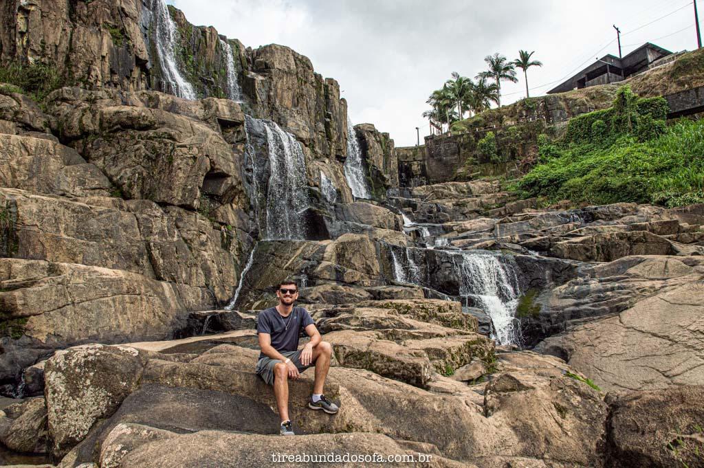 Rapaz sentado nas pedras do Salto Donner, no centro de doutor pedrinho