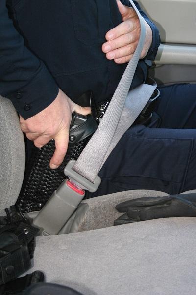 La mano de apoyo pasa por debajo del cinturón y la mano fuerte empuña la pistola.