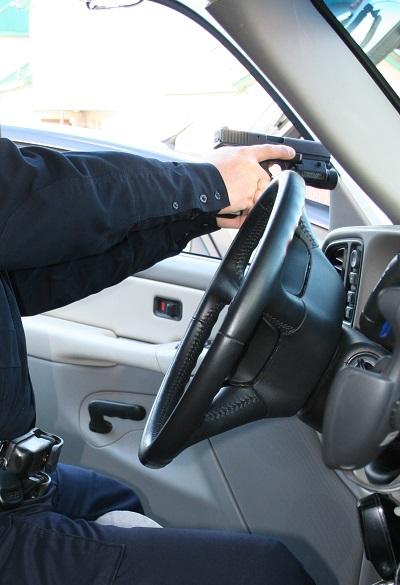 La boca de fuego apunta al frente con la pistola empuñada para disparar, pero sin meterla entre la puerta y el mástil del parabrisas del coche.