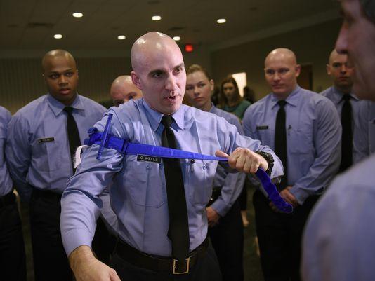 Curtis Wells, de 36 años, alumno de la Academia de Policía de Detroit, se coloca un torniquete en el brazo durante una demostración. (Foto: Clarence Tabb Jr./The Detroit News)