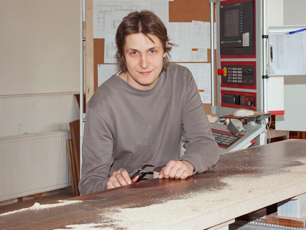 Tischlergeselle Nico Bose hat in unserer Tischlerei gelernt und bewahrt immer einen kühlen Kopf. Er bedient u.a. unsere größte Maschine, eine CNC-Fräsmaschine, versteht sich auf Computer und sorgt für deren reibungslosen Einsatz im Netzwerk.