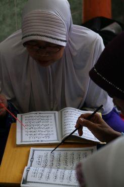 seorang nenek tengah belajar dengan metode ummi