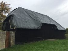 Tithe Barn with tarpaulin protecting thatched roof