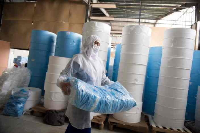 """AqQala, Iran – Jun 2020. Mojgan, 26, is a daily-paid worker at a workshop producing masks. Until the beginning of March, she had been working at a packing factory closed due to coronavirus outbreak and she was fired consequently, though got a one-year experience in the field. And after that, she could fortunately find a job as a worker at a workshop producing masks. During these three months that has been working at this workshop, she has only rested at home for a day, which was the second day of the Eid-e Nowruz, a two-week Iranian holiday, and except for that day has been working all the other days including the regular rest days. """"I hope coronavirus lasts longer so that I could work at this workshop for longer,"""" said she as a joke. Her daily earnings are as low as a dollar per day and she is not offered health insurance. """"Due to economic sanctions against Iran and coronavirus outbreak, I am currently and badly experiencing a rough financially time and even not hoping for getting married,"""" she added. This mask production workshop is located in an industrial region, 15 km from the city of Gorgan in north of Iran. This workshop, which is originally a manufacturer of fabric covers, suffered severe damage due to last year flood in northern Iran and declared bankruptcy. But with the outbreak of coronavirus, it was reopened and able to produce 140,000 sanitary masks a day, employing six women who had been fired particularly because of the pandemic. The workshop manager says that if the second wave of pandemic comes to Iran, they will be ready to produce 400,000 masks a day, if they are provided with the raw materials, which are often imported. ( Photo Credit: Hamed Barchian/ NVP Images"""