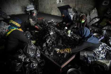 """Gorgan, Iran – Jun 2020. 34-year old Maryam, 35-year old Azadeh, and 37-year old Zahra are working in a charcoal packaging workshop. This manual charcoal packaging workshop that employs ten workers, six of whom are women, has been in business for four years. The workshop had been closed as many other businesses had due to coronavirus outbreak. """"After the workshop had been closed for three days, the employees were continually calling and asking to return to work; thereafter, we started working again at the request of the employees,"""" the workshop manager said. """"My husband, who is a construction worker, was out of work for two months due to coronavirus outbreak and if I along with my co-workers did not plead with our employer, I would be out of work too and would not know how to make a living,"""" Maryam said. It is indeed a truly laborious work that I do illegally these days. Nevertheless, to choose between the bad and the worse we have no option but to opt for the bad,"""" Zahra added. Azadeh, who is a mother of three, had been working at a kindergarten before coronavirus outbreak, however, since the closure of educational centers due to coronavirus pandemic, charcoal packaging has been the only job she could take so far. """"I come neat and clean each day to work but go back home all covered in black coal dust owing to our working environment,"""" she said. ( Photo Credit: Hamed Barchian/ NVP Images)"""