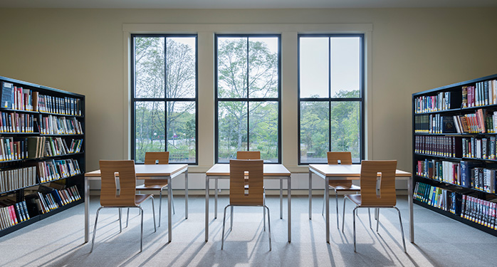 a photo of the back of the library that has two book cases on either side and 3 windows with 3 tables and 6 chairs between them