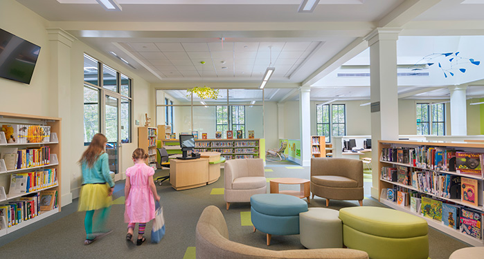 photo of the children's room picturing a seating area, shelves with books and DVDs, the check out desk, and two young girls walking