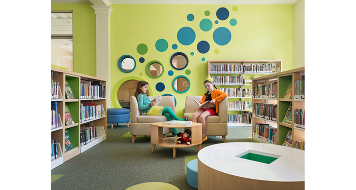 two girls sitting in chairs and reading in the fiction section inside of the children's room