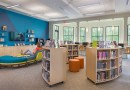 photo of the inside of the teen room of the library picturing the book shelves. seating areas, computers, TV, and two teen girls