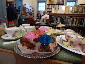 Photo odd many desserts, some with small umbrellas sticking out of them, in front of a group of people sitting at a table in the union library