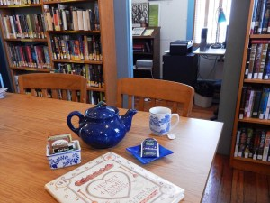 photo of a tea pot and mug next to tea bags and a book on a table in front of bookcases