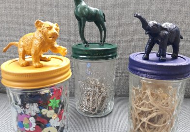 glass jars with painted animals on top. a lion, a giraffe, an elephant