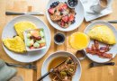 plates of breakfast food on a table. waffles pancakes eegs fruit bacon juice maple syrup