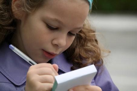 bambina con taccuino scrive con penna