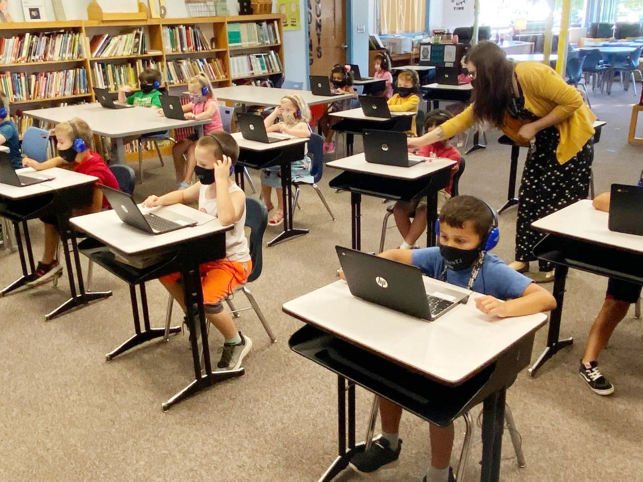 Teacher helps student on computer