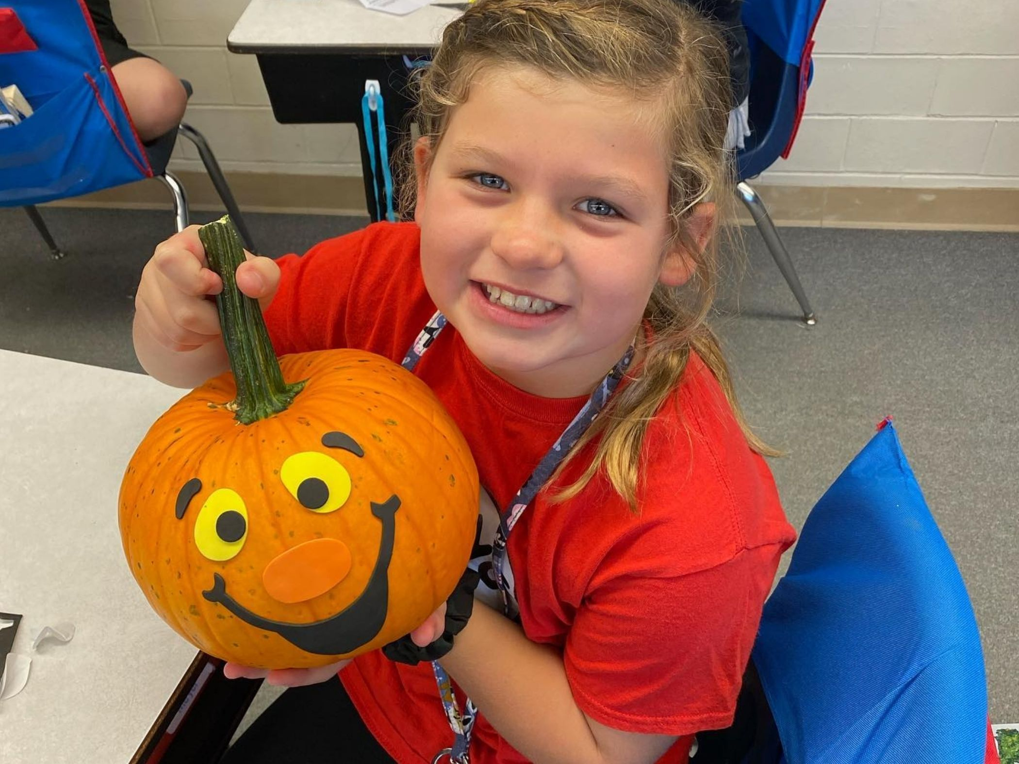 Student poses with her decorated pumpkin