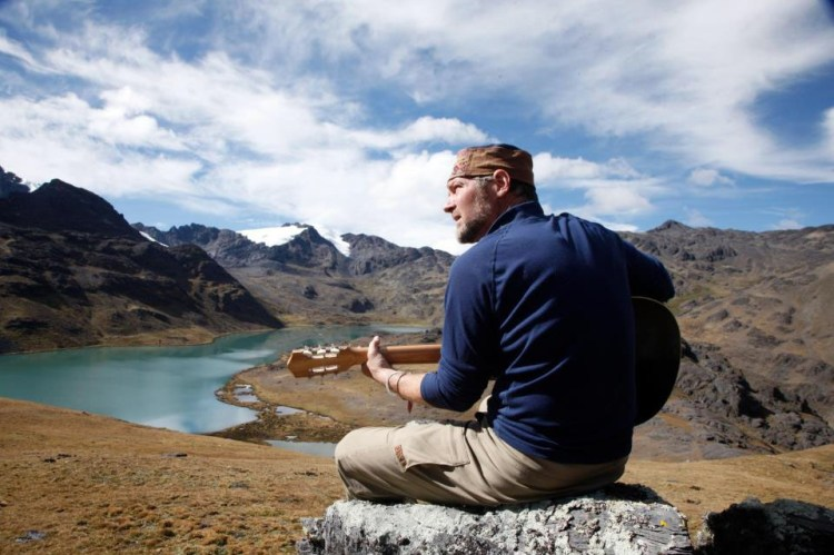 Survivorman playing a guitar in the wilderness.