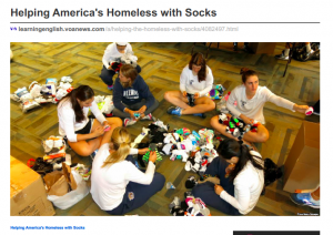 A photo from Voice of America's article about Helping America's Homeless with Socks. The article highlights The Joy of Sox®, a nonprofit that provides new socks for the homeless, and Tom Costello, Jr., founder and Chief Sock Person.