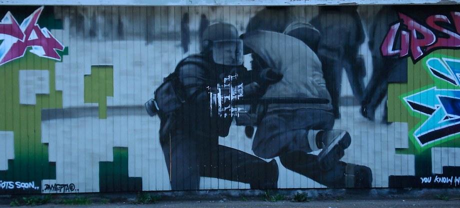 """Riot police graffiti"" by Benno Hansen is licensed under CC BY 2.0"