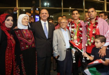Jordanian Prince Faisal bin al-Hussein (3L) poses for a photo with Ahmed Abughaush (3R) who won the men's 68-kg taekwondo competition at the Olympics in Rio de Janeiro to take home Jordan's first ever Olympic medal, and his family members during a welcome ceremony upon his arrival at the Queen Alia International Airport in Amman on August 23, 2016. / AFP PHOTO / Khalil MAZRAAWI
