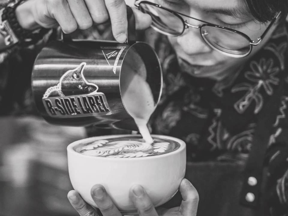 一個帶著眼鏡的男生一手拿著鋼杯一手拿著咖啡杯,有奶泡從鋼杯中流入杯子裡