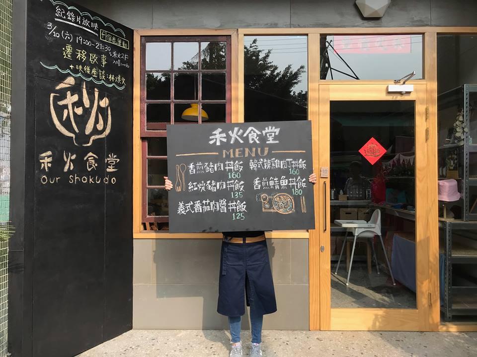 有個穿著黑色褲子的人站在門口舉著黑板,上頭有用粉筆寫著禾火食堂菜單