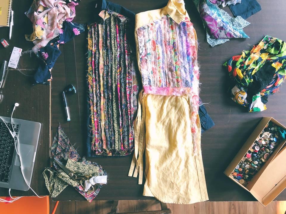 一件黃色一件藍色的襯衫,上頭都有碎花拼布,旁邊有一盒鈕扣、一台筆電、一堆碎布