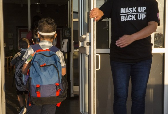 A staff member holds the door open for kids on the first day of school at Goodwin Frazier Elementary School in New Braunfels, Texas on Tuesday, Aug. 25, 2020.