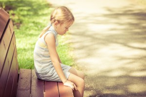 little girl with anxiety sitting on a park bench