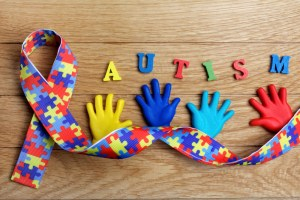 Autism awareness concept with colorful hands on wooden background