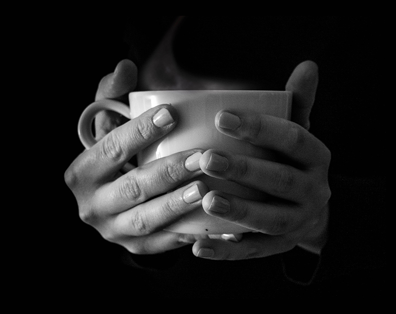 Hands holding a warm cup of tea