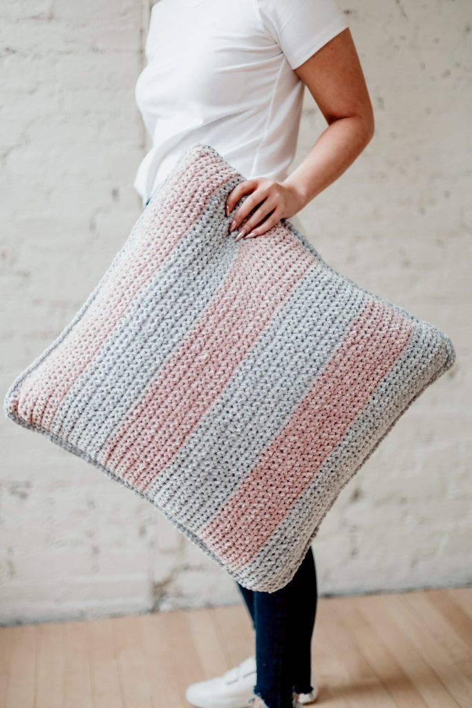 Spruce up your boring home decor with the Maisy Velvet pillow, a FREE beginner-friendly oversized throw pillow pattern from TLYCBlog. Pick your favorite velvet (chenille) yarn in three coordinating colors and bring together broad stripes and subtle details to give your living room a much-needed refresh. Perfect for beginners, this pattern uses simple stitches and works up quickly. Get the FREE pattern on the blog along with details on yarn choice and size. | TLYCBlog.com.