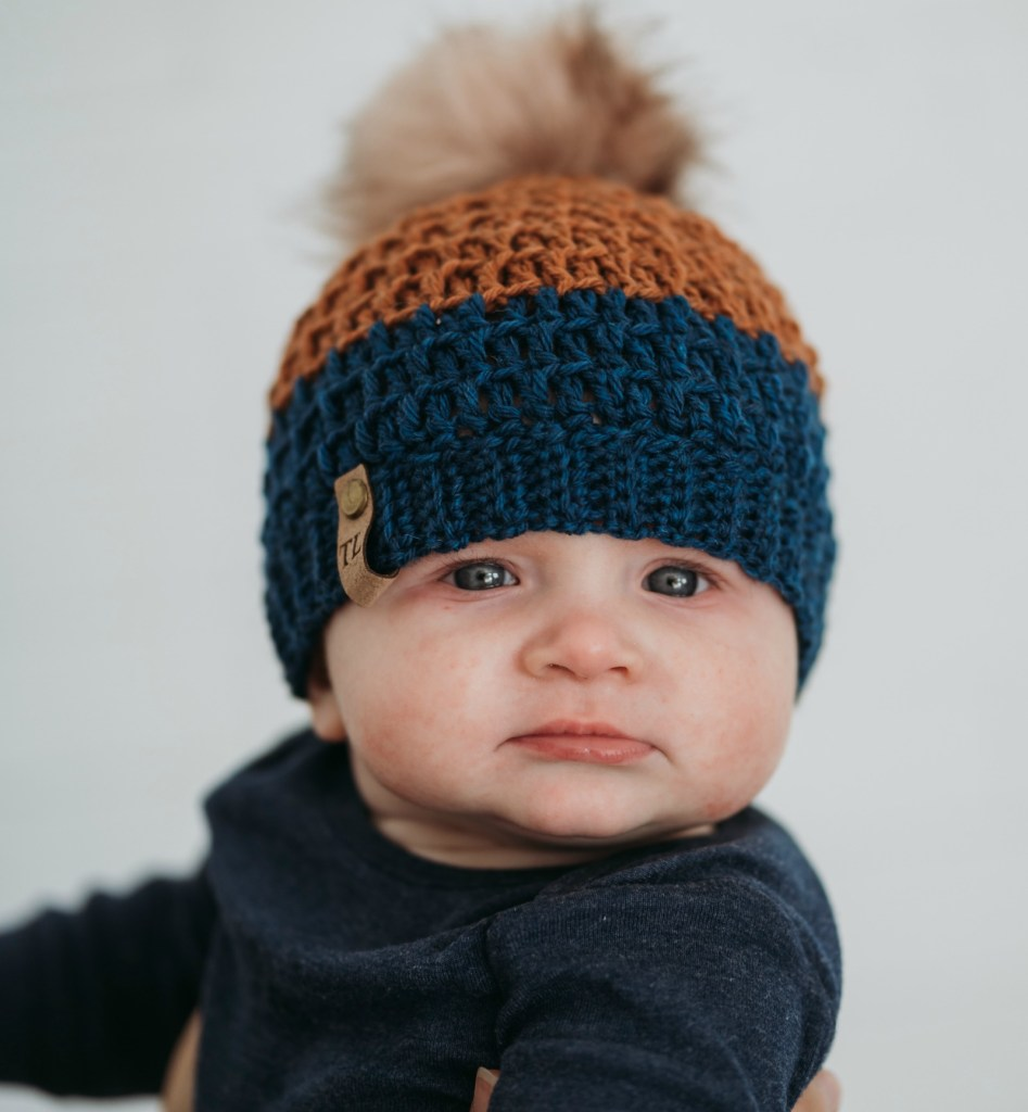 Mega Pom Beanie | Looking for a unique crochet slouchy hat that is perfect for the whole family? Try the Mega Pom Beanie, the ideal winter crochet hat pattern that includes sizes Newborn, 0-6 months, 6-12 months, 1-3 years, 3-10 years, and Teen/Adult. Babies, children, teens, and adults will love wearing this trendy hat, and you'll love making it. Beginner-friendly, it's one project you won't get enough of. Try the Mega Pom Beanie crochet hat pattern now. | TLYCBlog.com