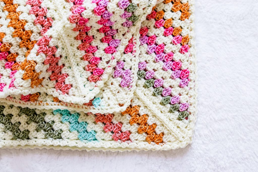 Make the Daphne Afghan, a free beginner friendly crochet granny stripe baby blanket. Use vibrant color changing yarns to make this pattern pop. It's fun, fast, and easy, and you'll be planning the next one before the first one is finished! Crochet this baby blanket for a girl or a boy. This simple and quick crochet baby blanket pattern is gender neutral, simple, and look great every time. | TLYCBlog.com