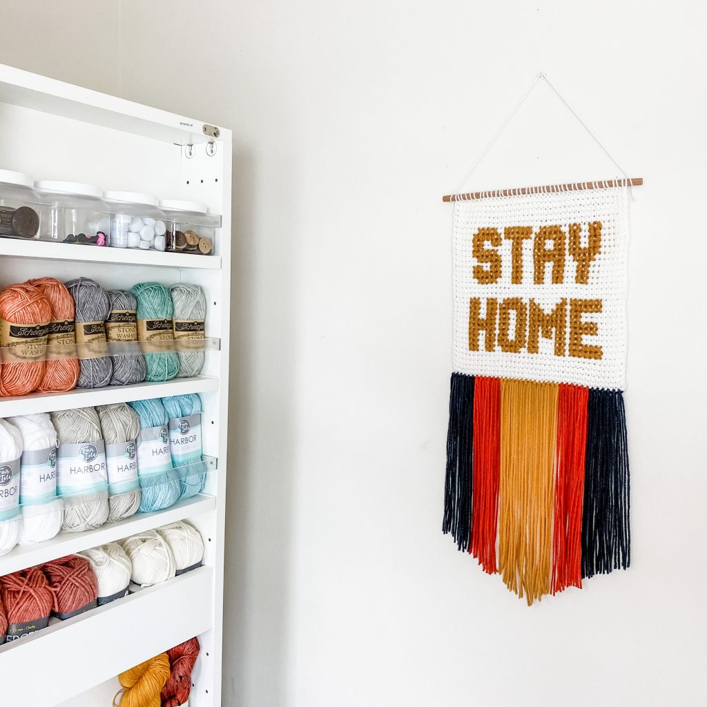 Make the Stay Home wall hanging, made from adding cross stitch to Tunisian crochet. Free crochet pattern! Experiment with fun colors and fringe with this COVID-19 quarantine Corona virus inspired wall art wall decor. | TLYCBlog.com
